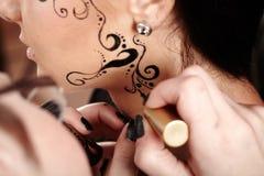 Morenita que aplica el tatuaje de la cara por el artista de maquillaje Imagen de archivo libre de regalías