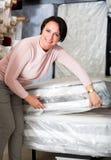 Morenita que elige el colchón el dormir Foto de archivo libre de regalías