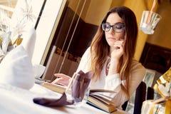 Morenita que lee un libro en un restaurante Imagenes de archivo