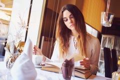 Morenita que lee un libro en un restaurante Fotografía de archivo libre de regalías
