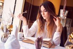 Morenita que lee un libro en un restaurante Fotografía de archivo