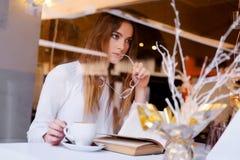 Morenita que lee un libro en un restaurante Fotos de archivo