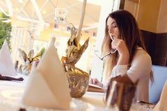 Morenita que lee un libro en un restaurante Foto de archivo libre de regalías