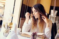 Morenita que lee un libro en un restaurante Imagen de archivo