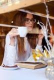 Morenita que lee un libro y que bebe un café Fotos de archivo libres de regalías