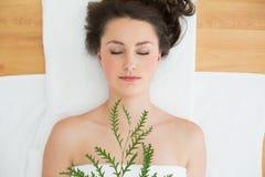 Morenita que miente con las hojas en salón de belleza Imagen de archivo