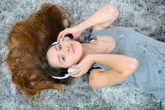 Morenita que pone en piso con los auriculares encendido Imagen de archivo libre de regalías