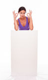 Morenita que pone mala cara sana detrás del cartel en blanco Fotos de archivo libres de regalías