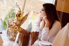 Morenita que se sienta en un restaurante Fotos de archivo libres de regalías