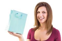 Morenita que sostiene un bolso del regalo que sonríe en la cámara Imagen de archivo libre de regalías