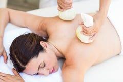 Morenita que tiene masaje con las compresas herbarias Foto de archivo libre de regalías