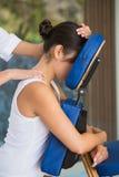 Morenita relajada que consigue un masaje en silla Foto de archivo libre de regalías