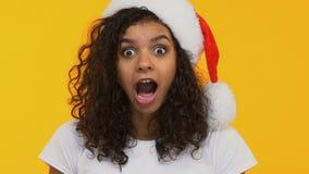 Morenita rizada en el sombrero de Papá Noel que dice el wow, sorprendido con el regalo de Navidad, humor festivo almacen de video