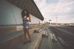Morenita rizada hermosa usando su smartphone Fotos de archivo
