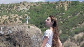Morenita sensual con el pelo largo en un vestido blanco corto ligero en un barco en un día ventoso almacen de metraje de vídeo