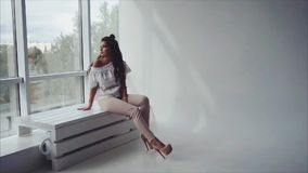 Morenita sensual de la mujer bastante joven que plantea sentarse cerca de la ventana almacen de metraje de vídeo
