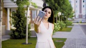 Morenita seria joven en el vestido blanco que presenta para el selfie que sostiene smartphone en fondo de la calle almacen de video
