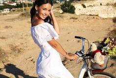 Morenita sonriente bonita en el vestido elegante que se sienta en la bicicleta Foto de archivo