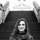 Morenita sonriente con el pelo largo, los labios sensuales y el maquillaje profesional colocándose en la calle Retrato blanco y n Foto de archivo libre de regalías