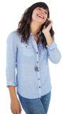 Morenita sonriente con su teléfono móvil que llama alguien Foto de archivo libre de regalías