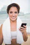 Morenita sonriente deportiva con la toalla alrededor del cuello que sostiene smartphone Imagen de archivo libre de regalías