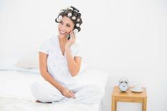Morenita sonriente en rodillos del pelo en el teléfono en cama Imagen de archivo