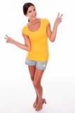 Morenita sonriente feliz que gesticula el signo de la paz Fotografía de archivo