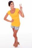 Morenita sonriente feliz que gesticula el signo de la paz Fotos de archivo