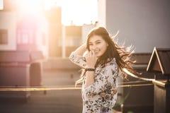 Morenita sonriente hermosa que se sostiene el pelo en las manos imagen de archivo