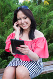 Morenita sonriente que escucha la música con la tableta Fotos de archivo