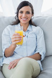 Morenita sonriente que ofrece el zumo de naranja a la cámara Fotos de archivo libres de regalías