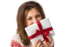 Morenita sonriente que sostiene un regalo con la cinta roja Imagen de archivo