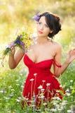 Morenita voluptuosa joven que sostiene un ramo de las flores salvajes en un día soleado Retrato de la mujer hermosa con la presen Imagen de archivo libre de regalías