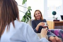 Morenita y comunicación rubia mientras que bebe el café en livin Foto de archivo libre de regalías
