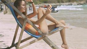 Morenos delgados de la muchacha en silla plegable en la playa de la arena