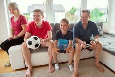 Morföräldrar, deras son och sonsonen spelar dataspelen Arkivfoton