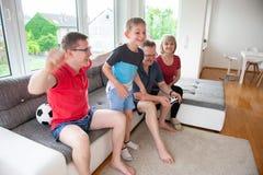 Morföräldrar, deras son och sonsonen spelar dataspelen Arkivbilder