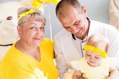 Morföräldrar firar sondotterns födelsedag Horisontalsoligt foto royaltyfria bilder
