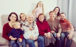 Morföräldrar 60-70 gamla år med barn fotograferar bes Arkivfoto