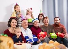 Morföräldrar 65-75 gamla år med barn fotograferar bes Arkivfoton