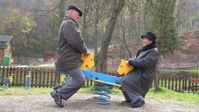 Morföräldrar kopplar ihop att ha gyckel på barnlekplatsen som ler att skratta i natur stock video