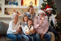 Morföräldrar med barn som mousserar med jul, mousserar Arkivfoto