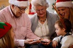 Morföräldrar med barn som ser julfoto på cellphon Royaltyfri Bild