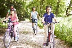 Morföräldrar med barnbarn som cyklar i bygd arkivbild