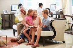 Morföräldrar med barnbarn som sitter i hotelllobby Royaltyfri Foto