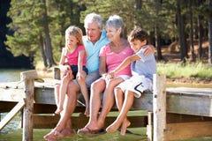 Morföräldrar med barnbarn som sitter vid en lake royaltyfria foton
