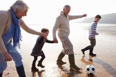 Morföräldrar med barnbarn som spelar fotboll på stranden Arkivbild