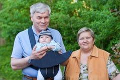 Morföräldrar med det förtjusande barnbarnet arkivbilder