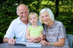 Morföräldrar med det hållande ögonen på fotoalbumet för barnbarn arkivbilder