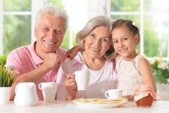Morföräldrar med sondottern som dricker te Arkivfoto